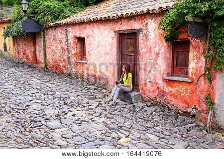 Young woman sitting at Calle de los Suspiros (Street of Sighs) in Colonia del Sacramento Uruguay. It is one of the oldest towns in Uruguay