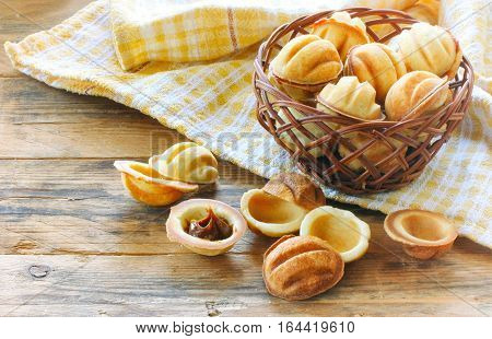homemade cookies shaped nuts with cream boiled condensed milk checked towel wicker basket on wooden table