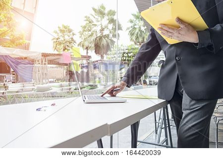 businessman hand working with new laptop and writing on the notepad Business concept vintage tone soft focus