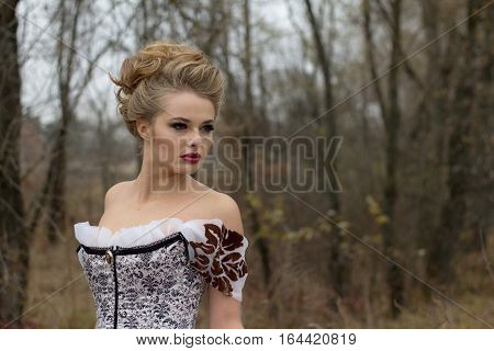 Beautiful young lady in gorgeous vintage white dress in the forest professional makeup and hairstyle. Late autumn cold. Portrait outdoors.