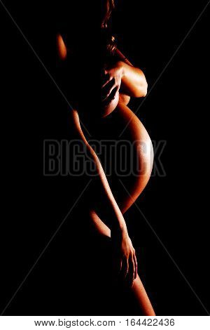 Naked pregnant woman covering her breast on black background.