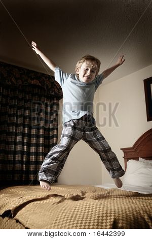 Young boy jumping on the bed