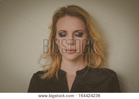 Close up portrait of a beautiful young blonde woman model with professional fresh daily make up on beige background. Eyes closed.