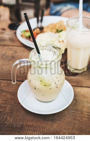 Frappe latte coffee green tea on wooden table with meals