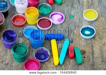 Set of gouache paints and watercolor for drawing artistic tools on old wooden background. Tools for creative work. Concept of back to school and creative art. Top view. Copy space.