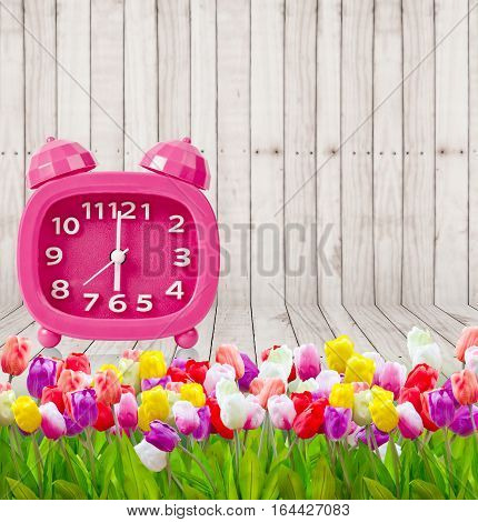 Bouquet of Tulips with vintage pink alarm clock a wooden background. Copy space
