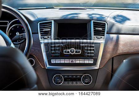 Car interior luxury. Beige comfortable seats steering wheel dashboard climate control speedometer display wood decoration.