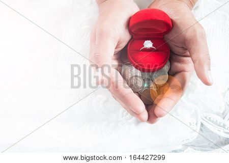 Saving money concept love couple relationship - close up of man giving diamond ring with money coin in hand