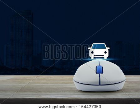 Wireless computer mouse with car front view flat icon on wooden table over city tower Internet service car concept