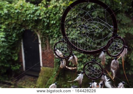 Dream catcher with one door in the brick wall and green trees as background