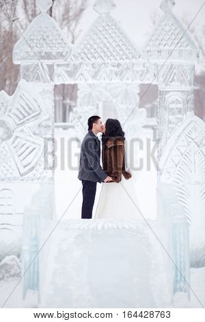 Wedding couple kissing in the middle of the ice figures in a snowy town, the bride in a fur coat and a white dress with a veil, the groom wearing a coat.