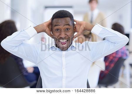 Furious black businessman tired of working on project at office. People in the background