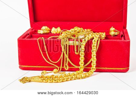 Group of gold necklace and gold ring of accessories in red box on white background.