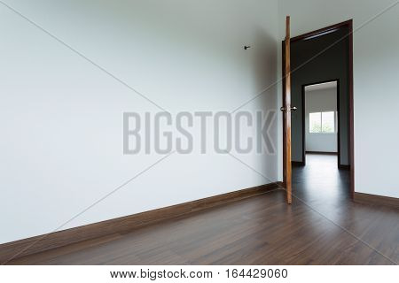 empty room interior with white mortar wall background and wood laminate floor and open wooden door