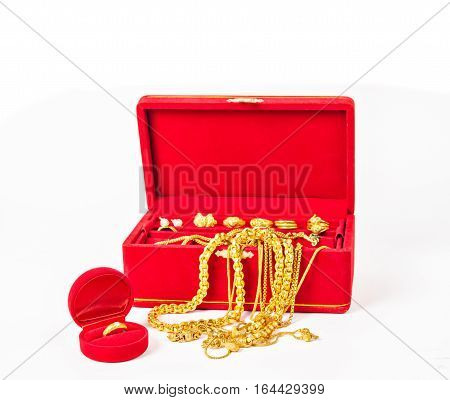 Group of gold necklace and gold accessories in red box isolated on white background.