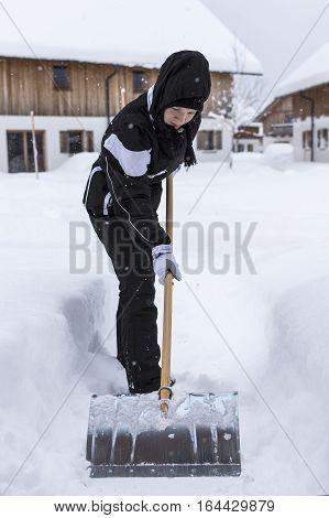 Removing Snow With A Shovel In The Snowfall
