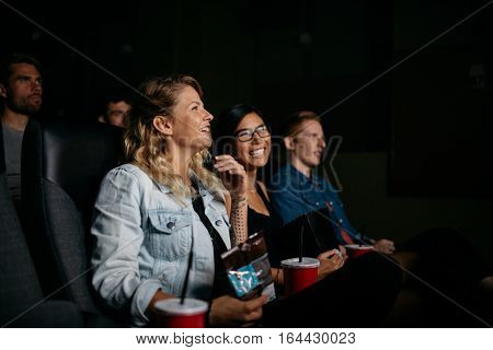 Group of friends sitting in multiplex movie theater and watching movie. Happy young people watching movie in cinema.