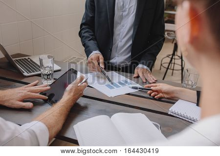 Close up shot of team of professionals meeting with digital tablet and charts. Business people discussing financial plan. Human hands pointing at graphs with pen.