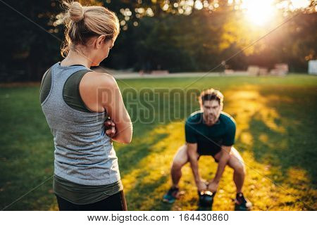 Female trainer standing in the park with young man doing weight training with kettlebell in background.