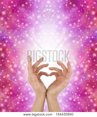 Sign Language for a Special Love - female hands touching pinkies  together to make a heart symbol with a white shaft of light behind and multiple sparkles on a vivid pink background