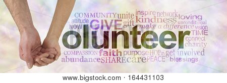We can volunteer together - male hand cupped by a female hand making the V of VOLUNTEER surrounded by a word cloud on a subtle multicolored background