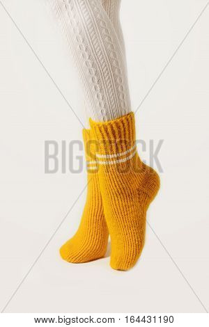 Female legs in white stockings and yellow knitted socks.