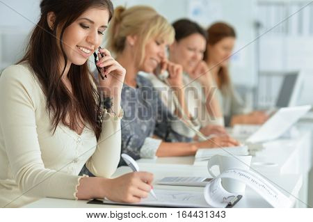 women working together in office, using digital devices