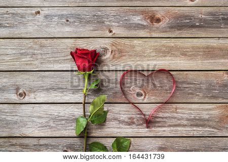 one red rose on wood background with heart from ribbon. Valentines Day background