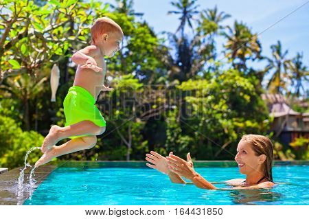 Happy child in action - active kid swim with fun in swimming pool. Baby son jump high to mother catching hands. Healthy family lifestyle summer vacation water sports activity and lessons with parents