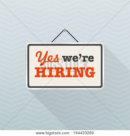 Simple white sign with text 'Yes we're hiring' hanging on a gray office wall. Creative business interior template for shop store. Human Resources employment recruiting concept. Vector illustration