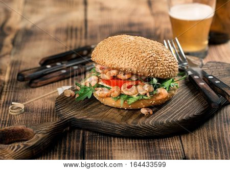 Burger with seafood on the old board on a wooden table with a glass of lager