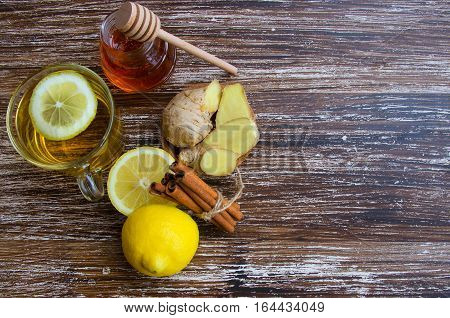 Hot cup of herbal ginger tea with lemonm spice and honey. Alternative treatment for cold or flu symptoms. Traditional medicine and natural health care concept. Copy space.