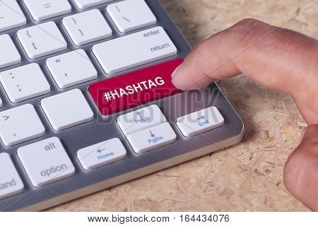 Man pressed keyboard button with hashtag word