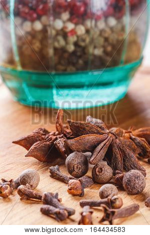 cloves, allspice, star anise on a wooden board closeup