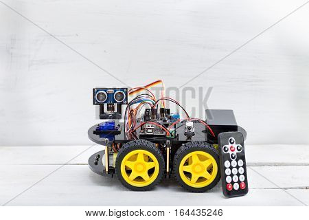 robot on four wheels and a variety of cables with remote control stands on a wooden background