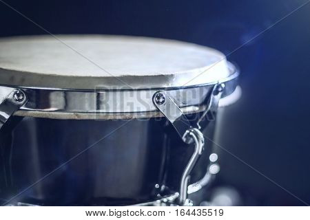 Goblet drum or darbuka, percussion musical instrument on dark background in rays of light stream