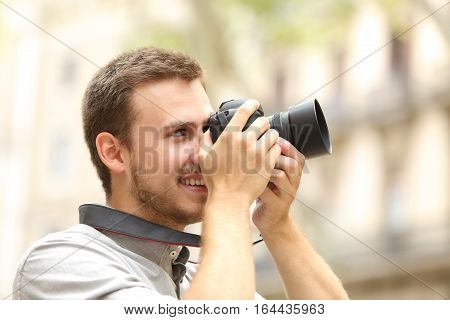 Side view of a happy man photographing with a dslr camera in the street of a city or town