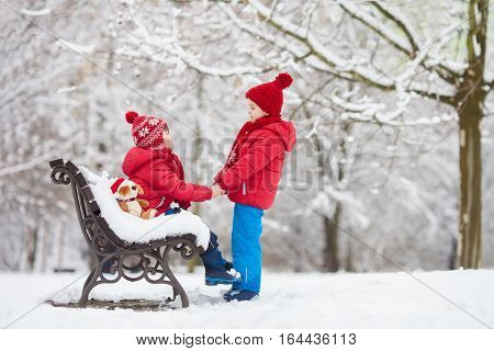 Two Adorable Children, Boy Brothers, Playing In A Snowy Park, Holding Hands, One Sitting On Bench