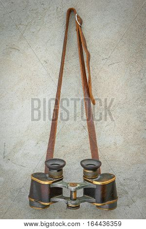 Old binoculars hanging on a concrete wall