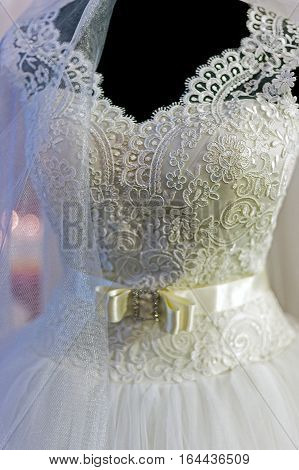 Detail of a wedding dress decorated with lace veils and knot.