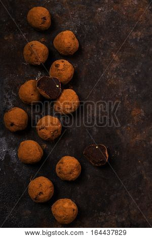 Dark chocolate avocado truffles sprinkled with cocoa on dark rusty metal background. Selective focus