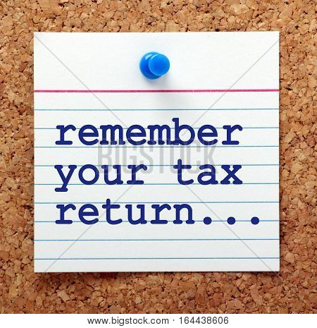 The words Remember Your Tax Return on a note card pinned to a cork notice board as a reminder to complete before the deadline