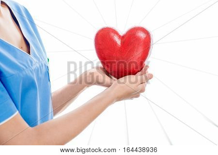 Female cardiologist in uniform holding red heart isolated on the white background. Close up view on the heart with no face