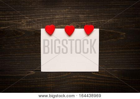 Valentine's day background. Valentine's Day card with red hearts on the wooden texture desk.
