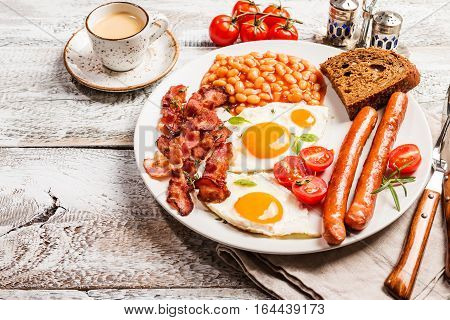 Traditional English Breakfast - sunny-side-up fried eggs, sausages, beans and bacon on white plate with coffee, top view