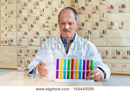 Chemist in lab coat filling colorful test tubes near periodic table