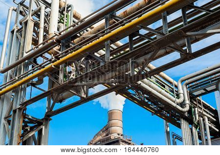 Chemical plant for factory with smokestack on blue sky.