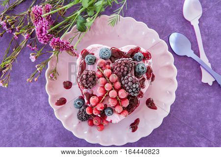 Ice cream in a heart-shape with berries