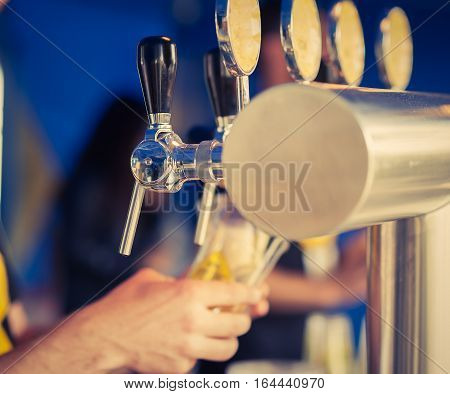 Barman hand at beer tap pouring a draught lager beer serving in a restaurant or pub.