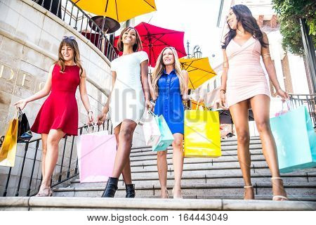 Multiethnic group of girls shopping - Four beautiful woman having fun while buying some presents in a mall